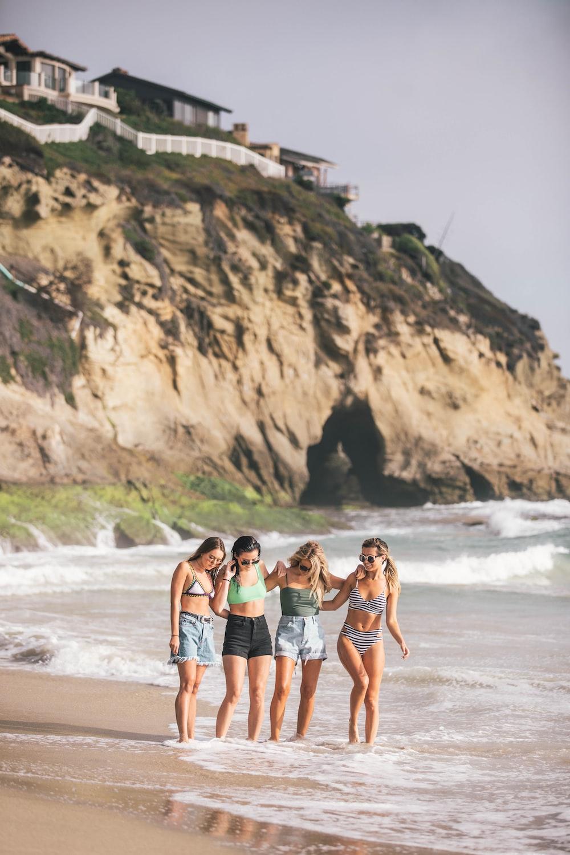 four women standing on seashore