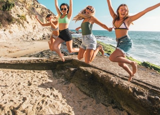 four women jumping in sea shore during daytime