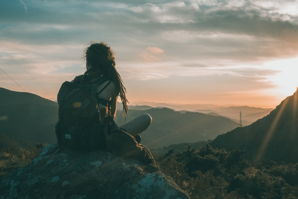 woman sitting on rock carrying black backpack
