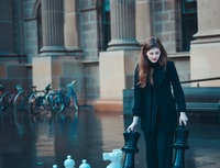 woman in black suit and pants standing near concrete pillar and bikes