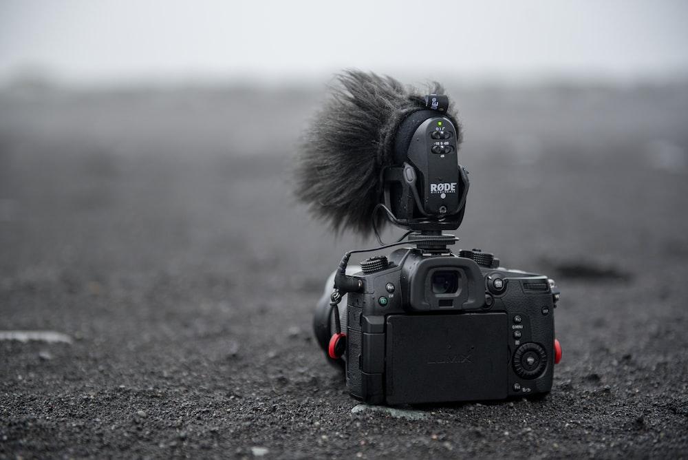 grayscale photo of DSLR camera on sand