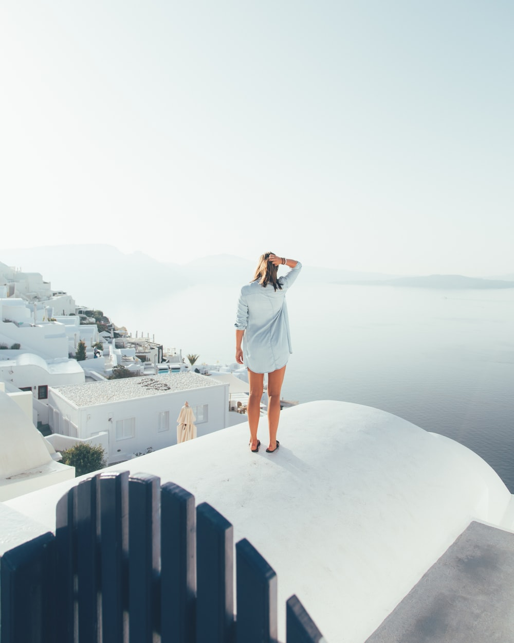 woman standing on concrete surface looking forward on sea