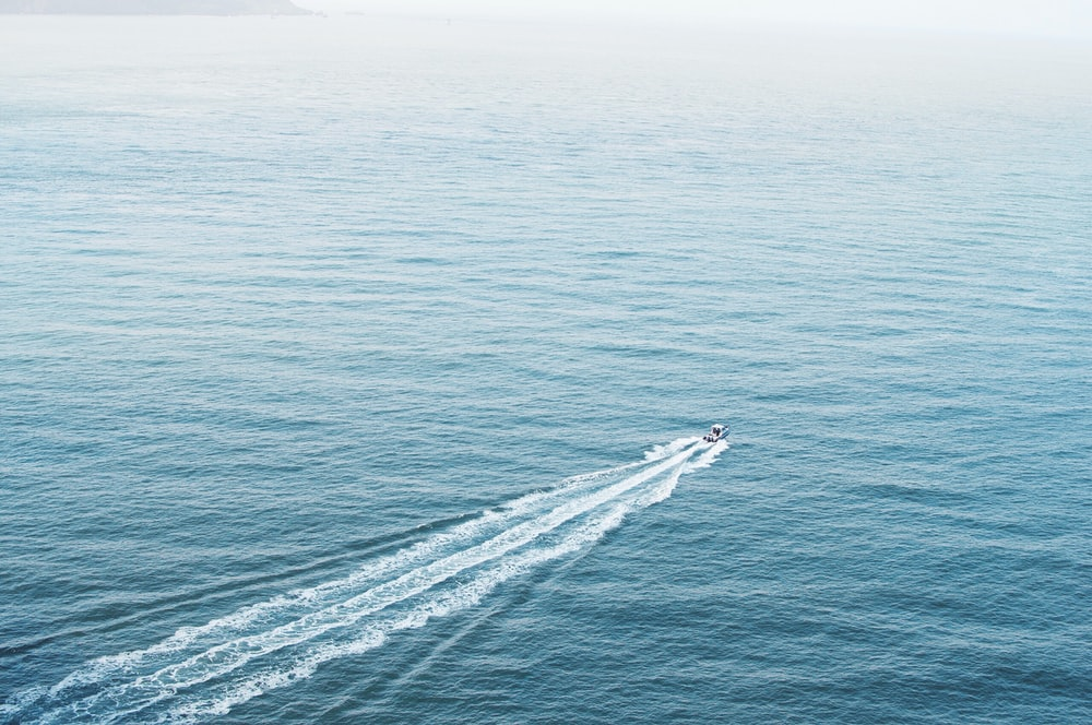 aerial photography of motorboat in middle of ocean