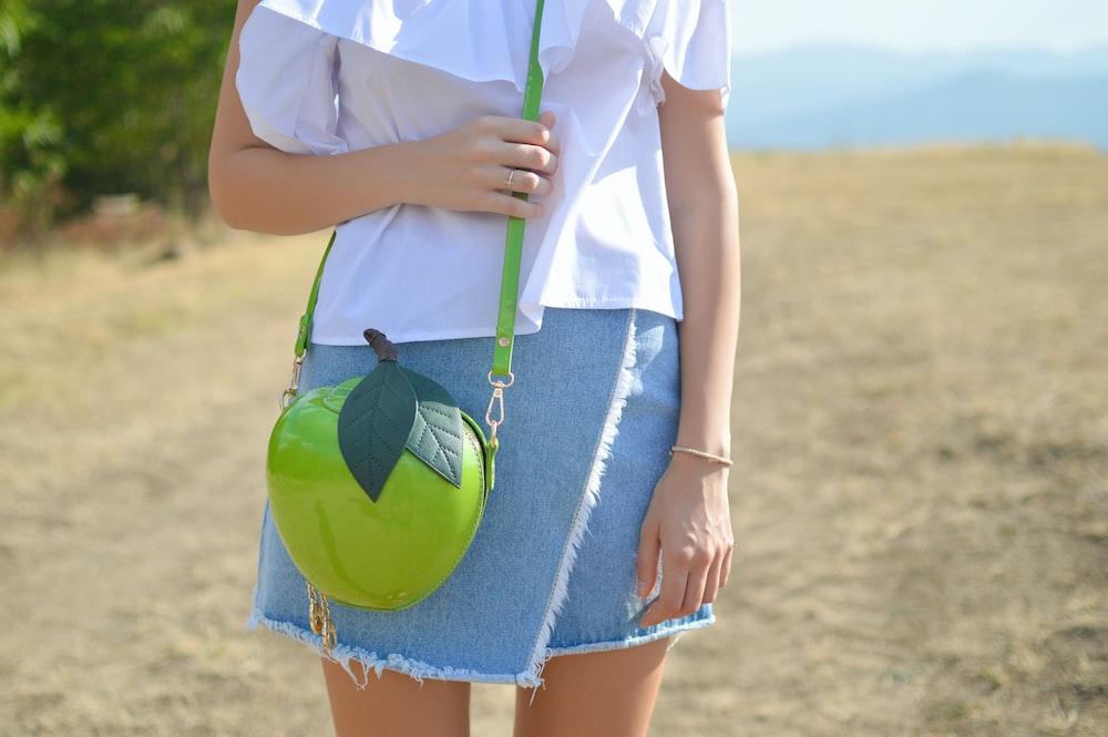 woman wearing green sling bag standing on brown soil