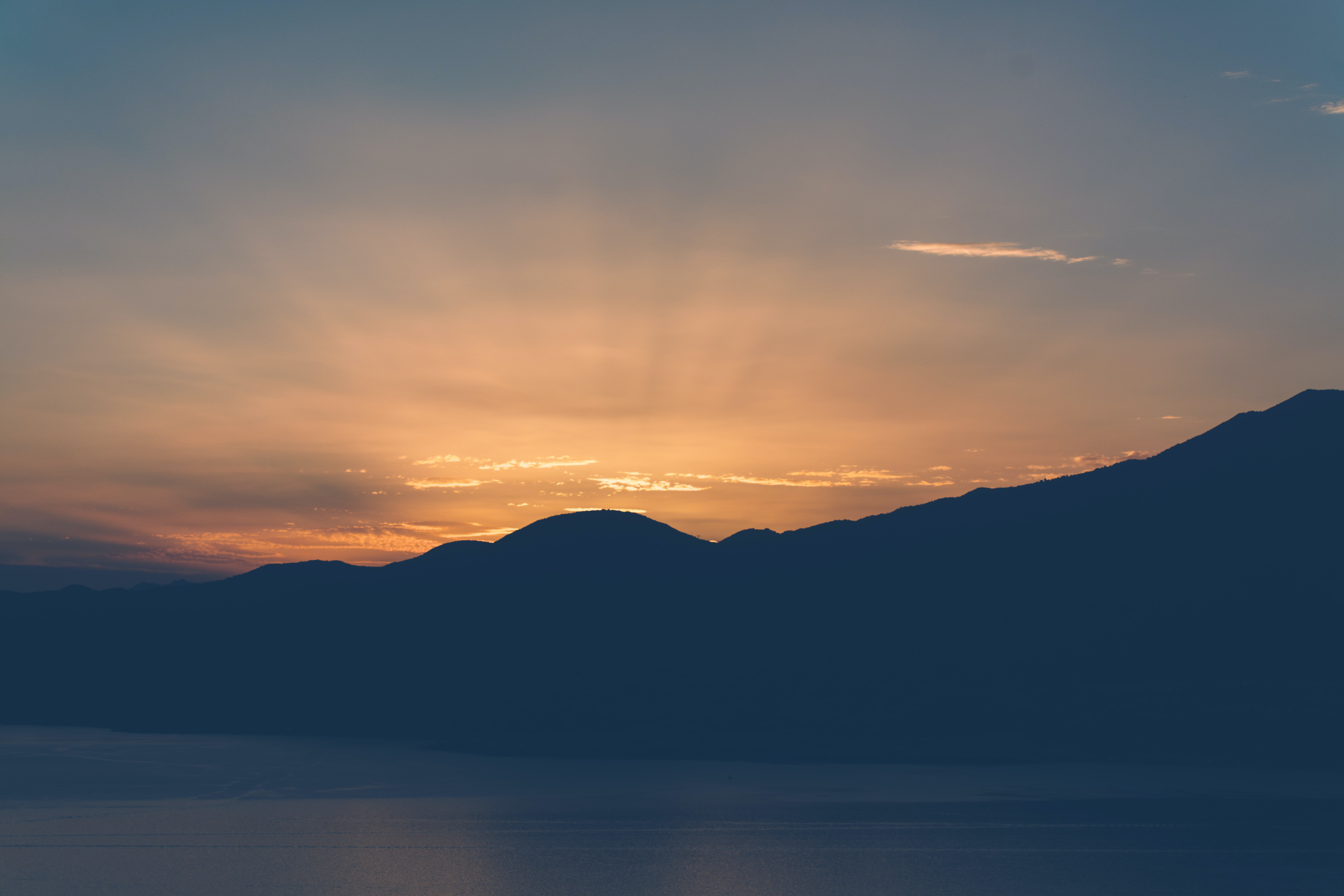 silhouette of mountains near body of water during golden hour