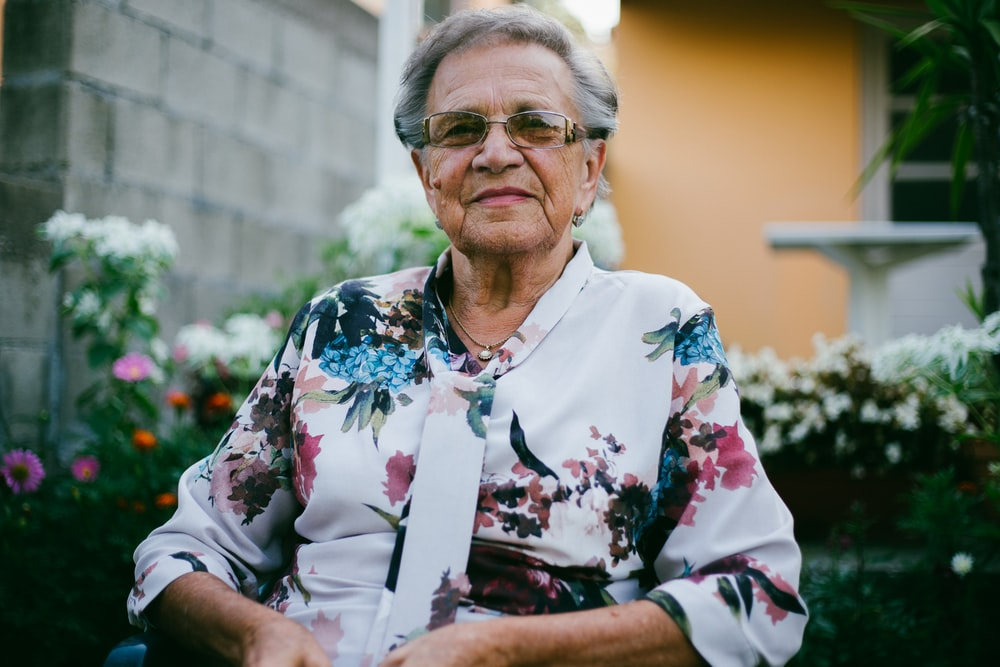 woman wearing white and multicolored floral top front of flower garden