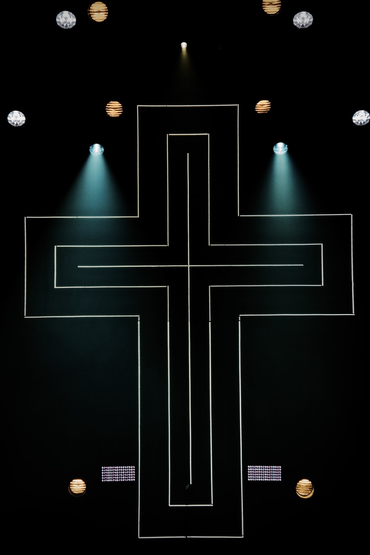 string lights cross on dark area with spot lights