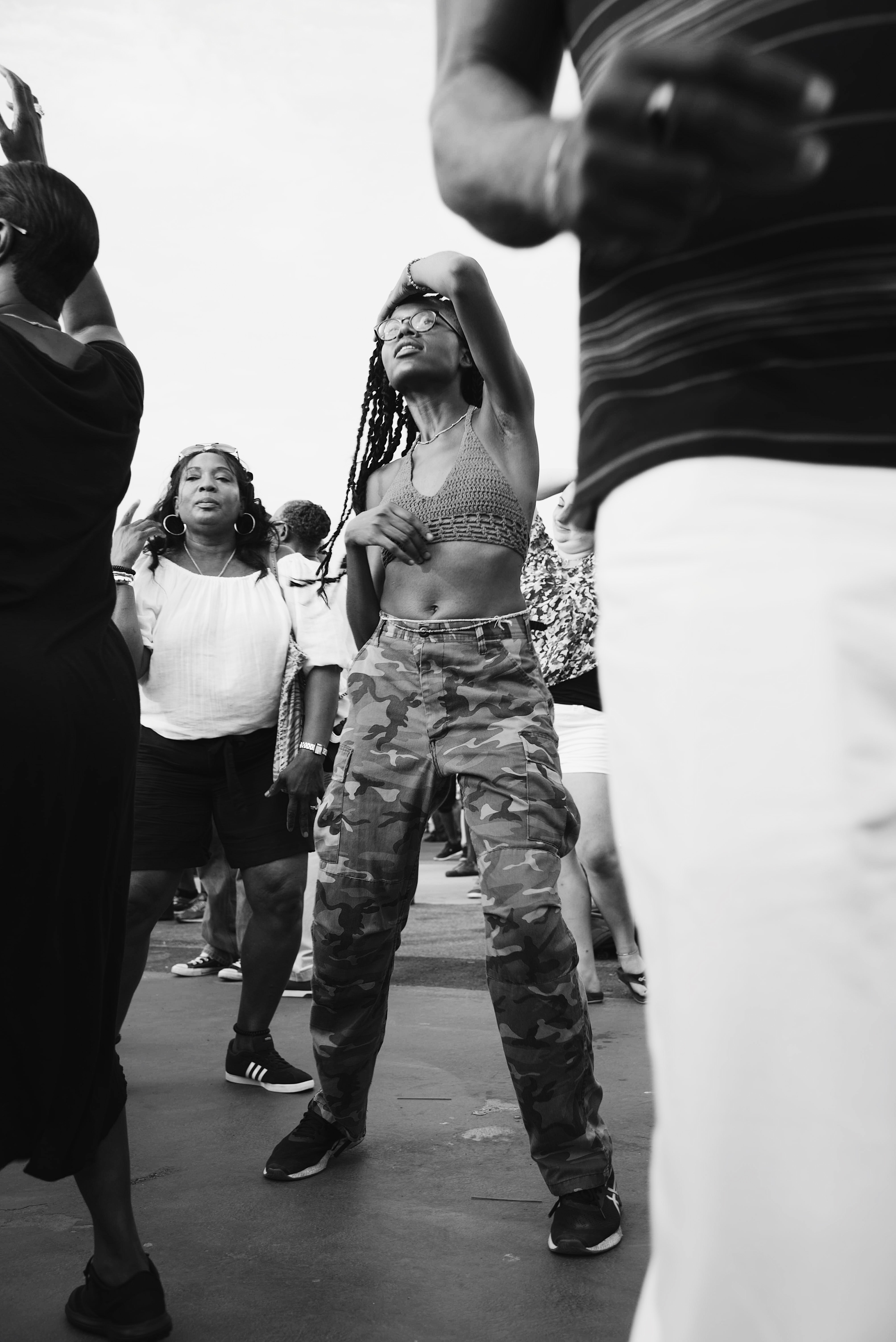 grayscale photo of woman dancing surrounded by people