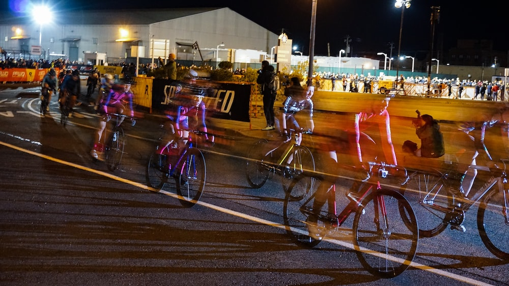 time lapse photography of a cyclists during night race