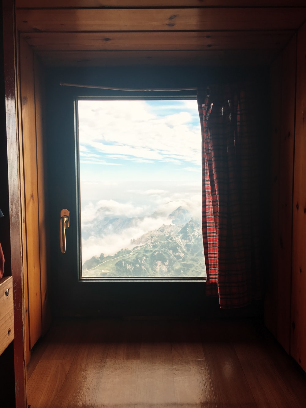 closed black wooden framed window with red plaid curtain