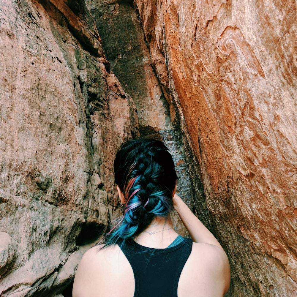 woman standing between brown rock formation