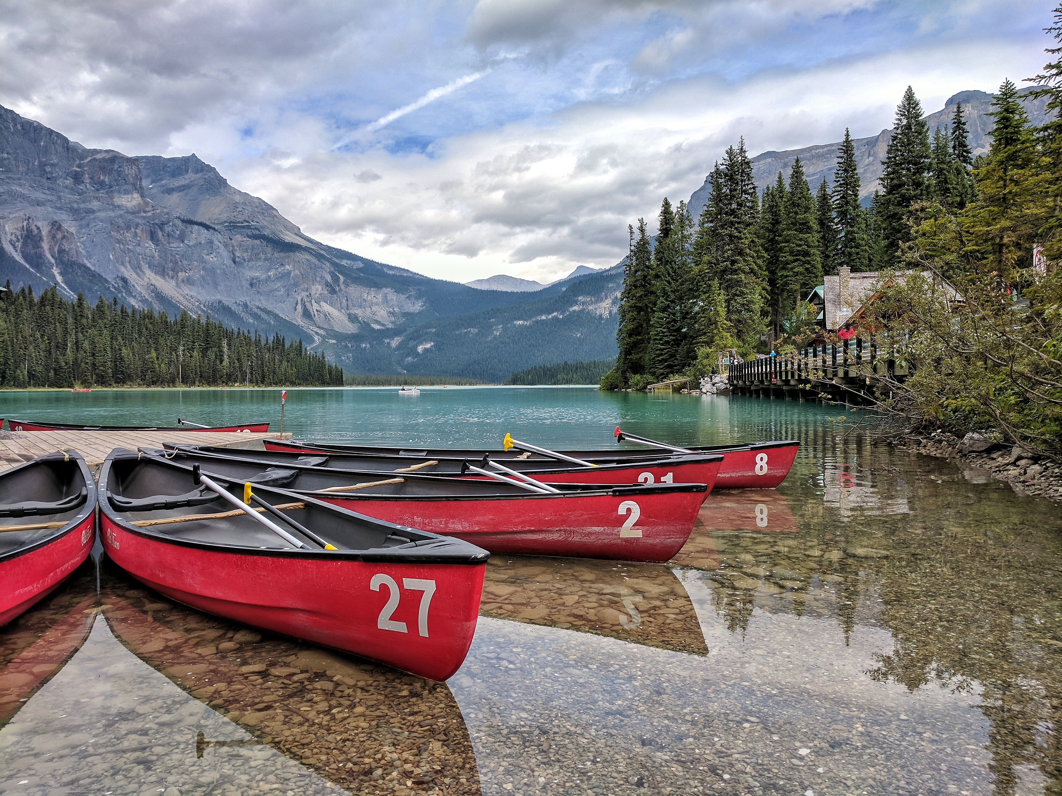 four red canoes on body of water