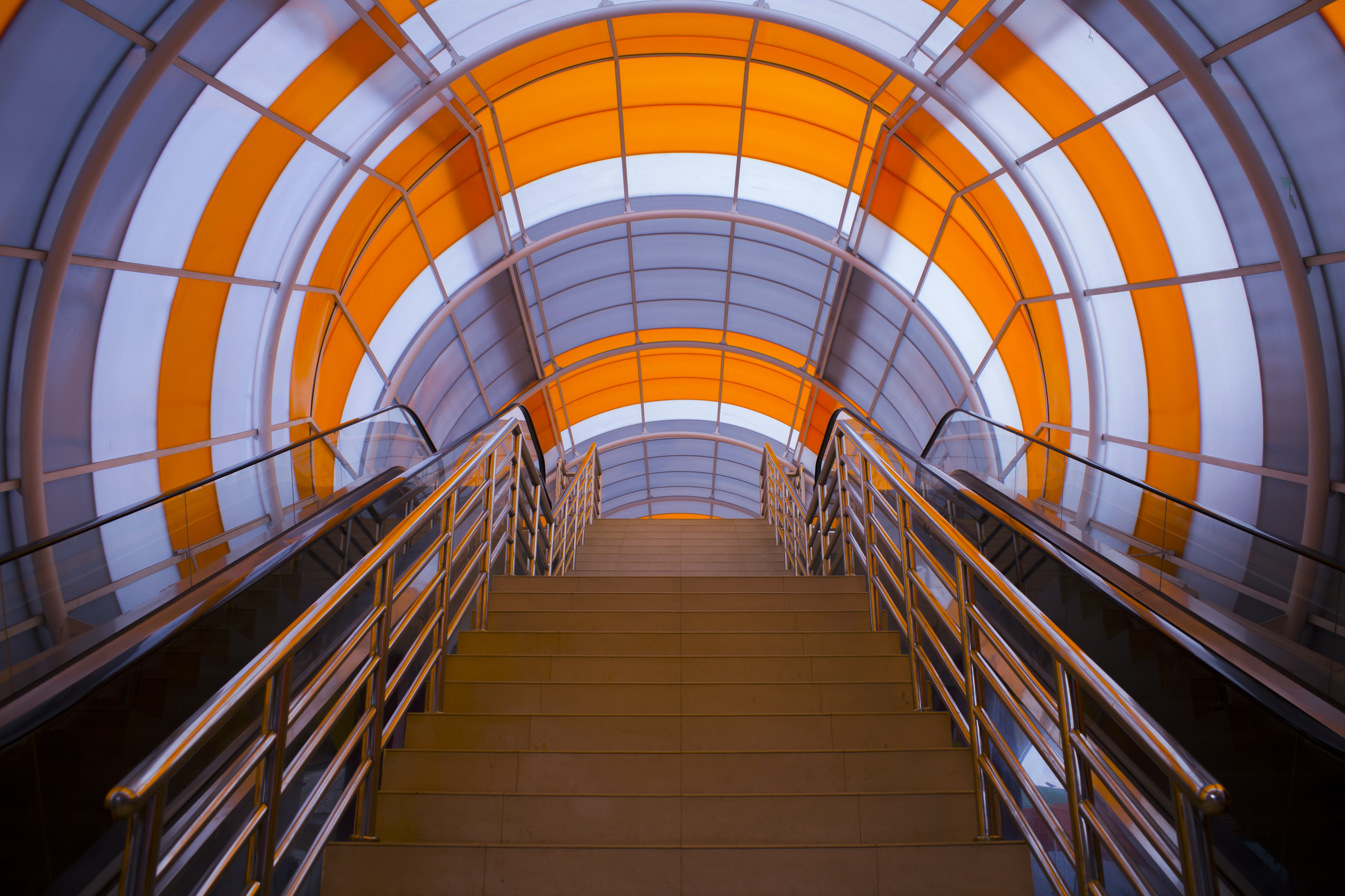 brown staircases with chrome handrails in gray and orange dome