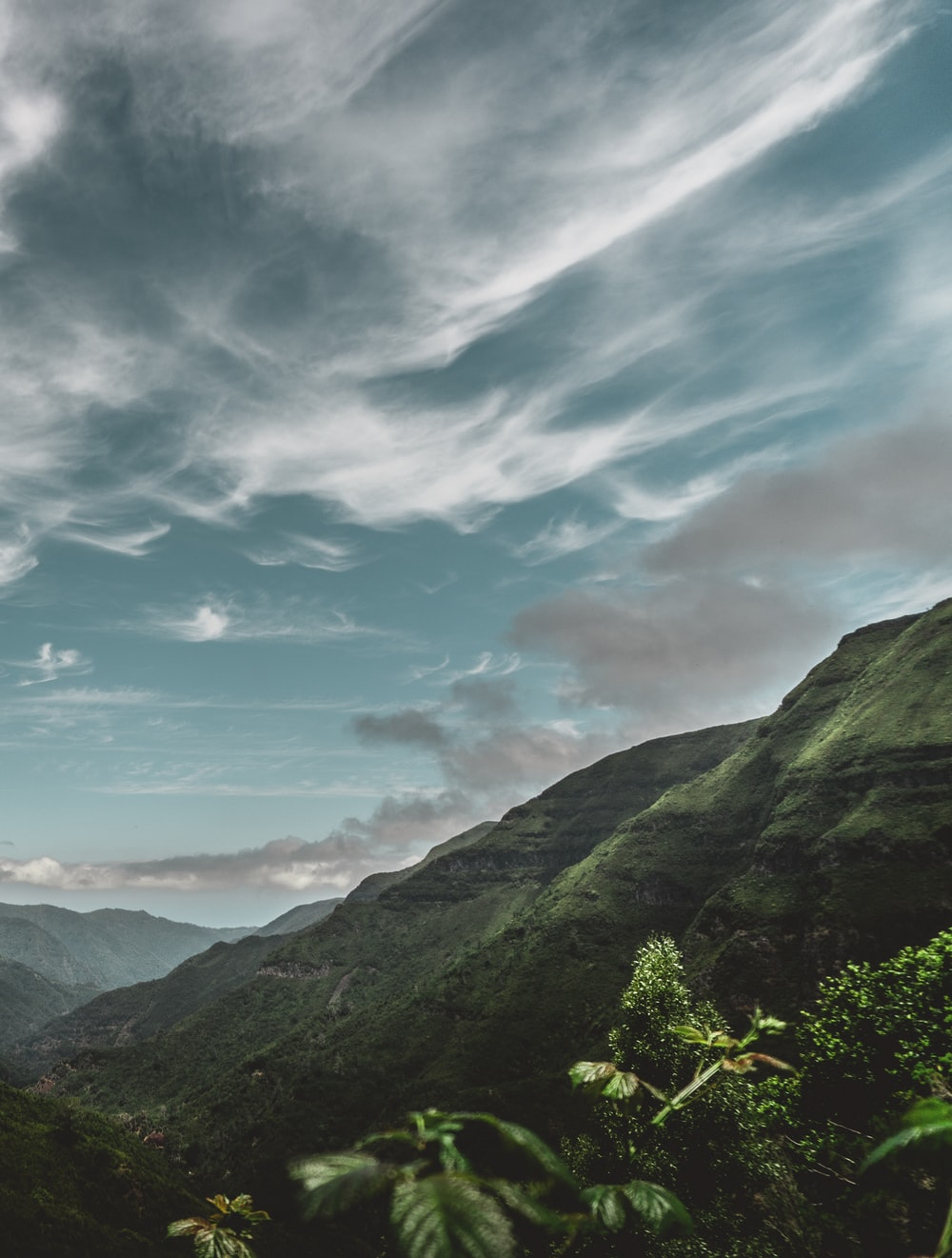green mountains under blue cloudy skies