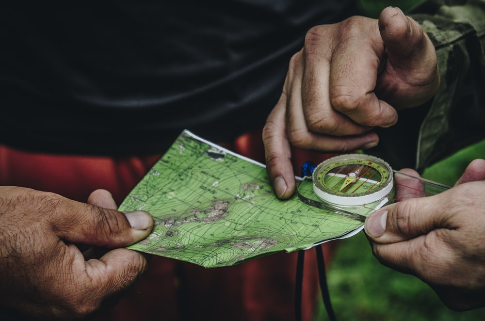 two person holding map and clear compass