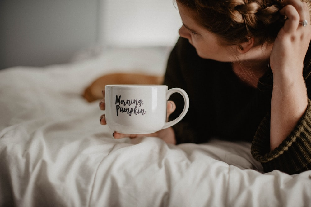 woman holding white mug while lying on bed