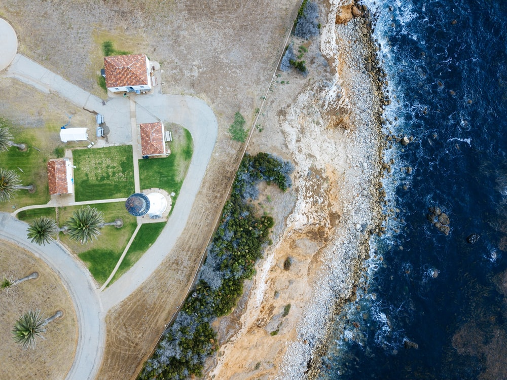 bird's-eye view photography of lighthouse nearby sea
