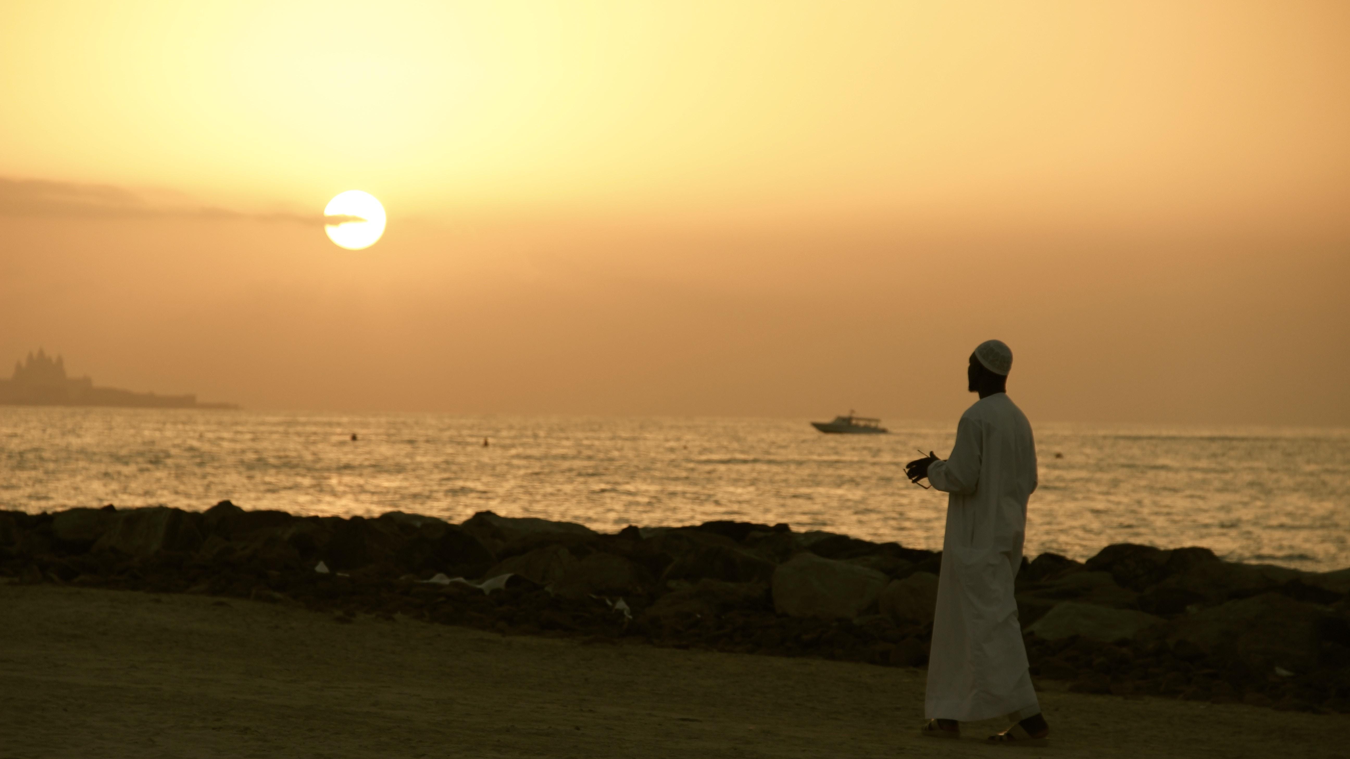 man walking on road beside shore