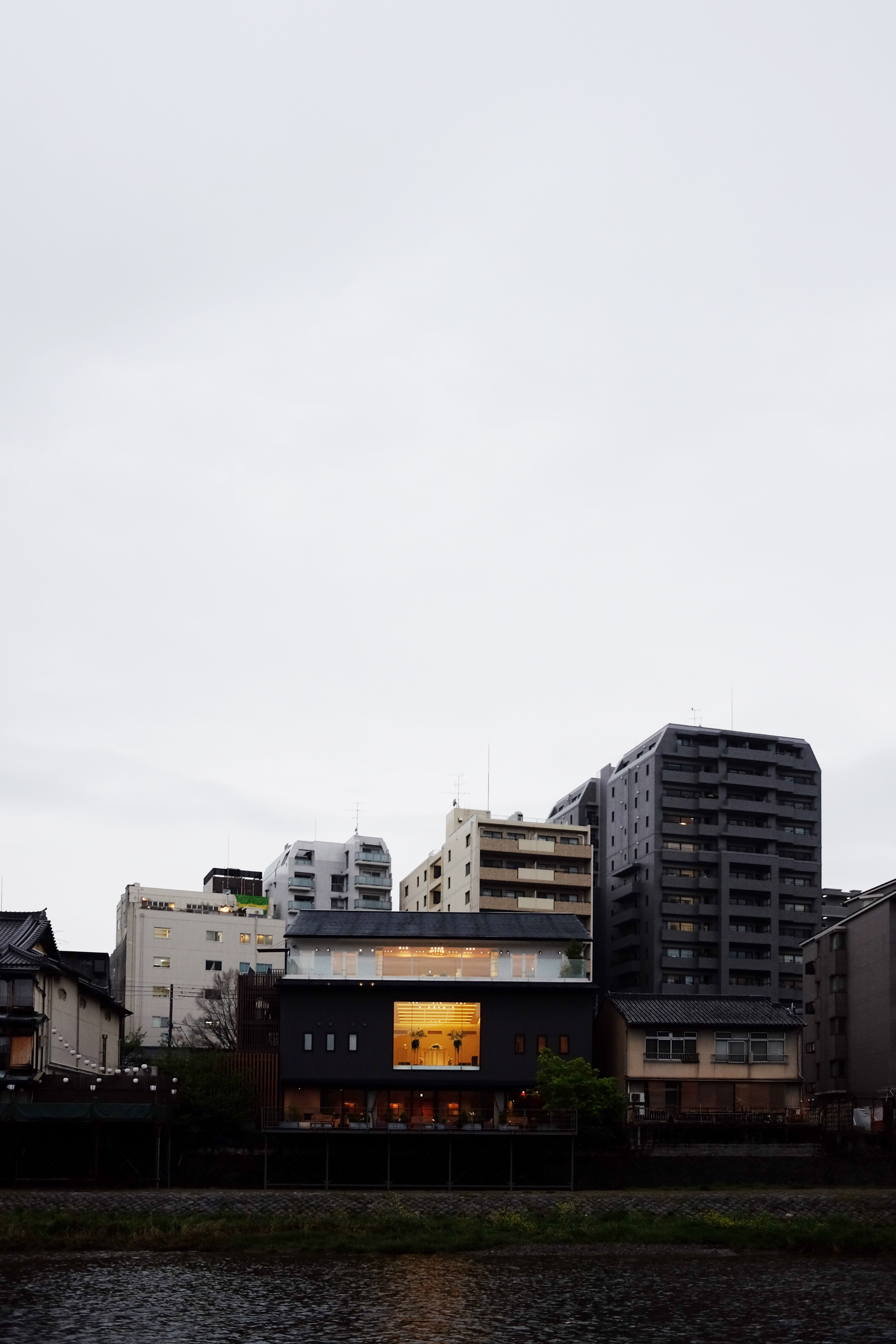 assorted-color concrete building near lake under cloudy sky