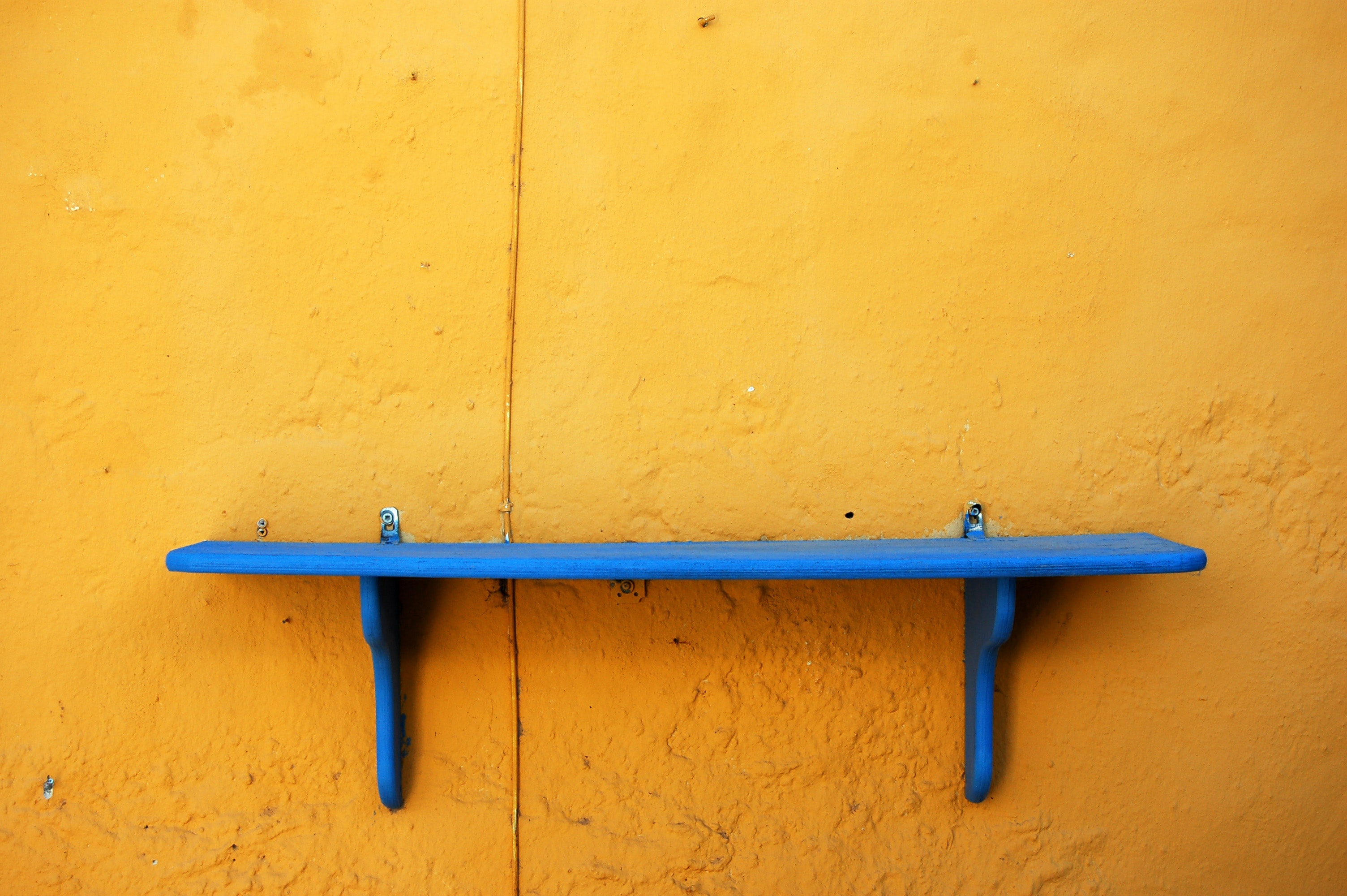 focus photography of blue wooden floating shelf