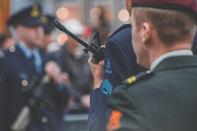 shallow depth of field photo of man holding rifle bagpipe teams background