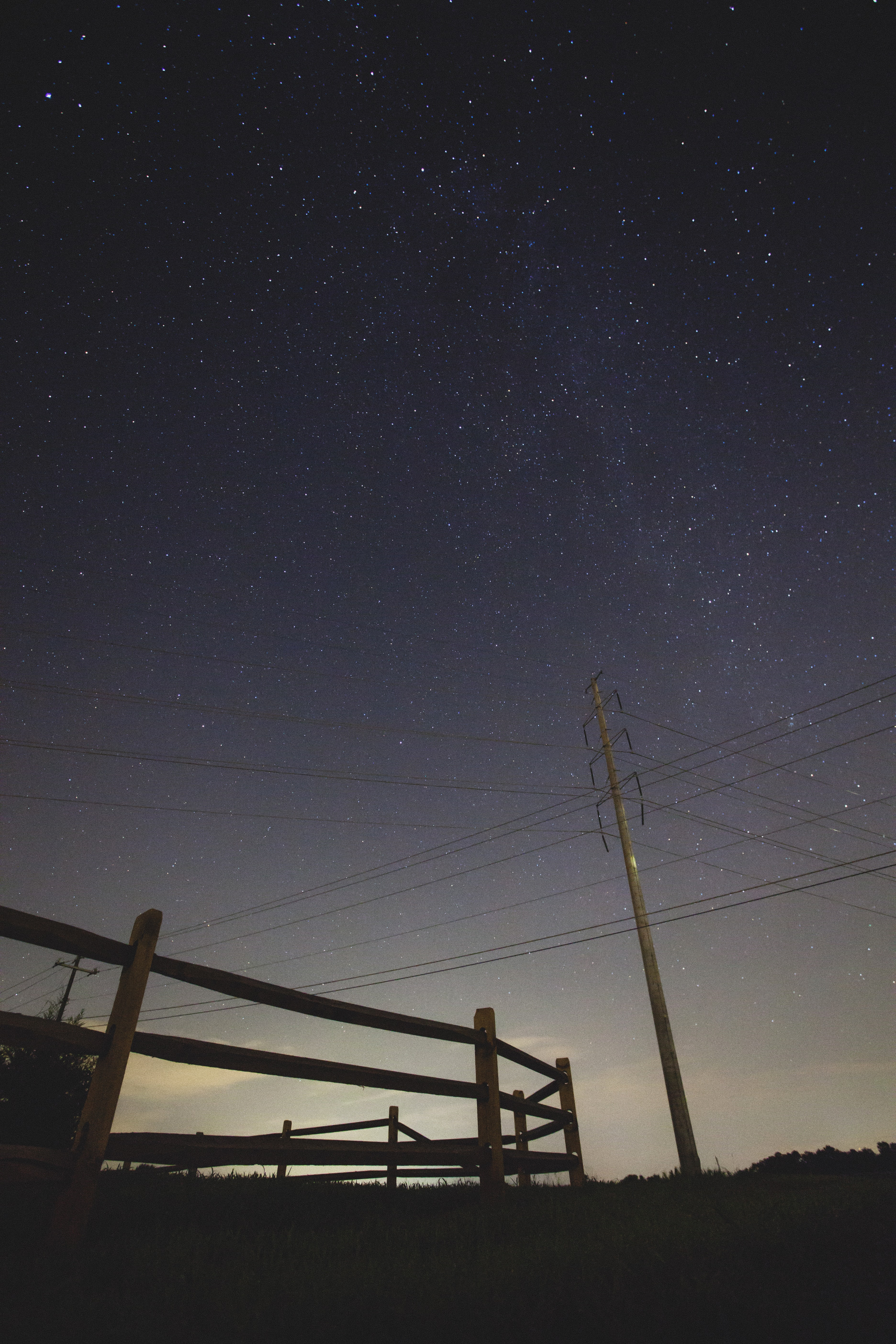 brown wooden fence and electrical post under stary skies