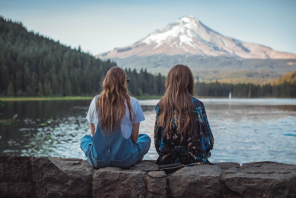 women sitting on rock near body of water