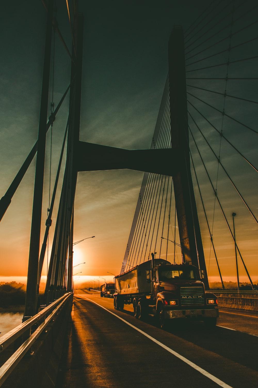 brown Maek freight truck on bridge during dawn