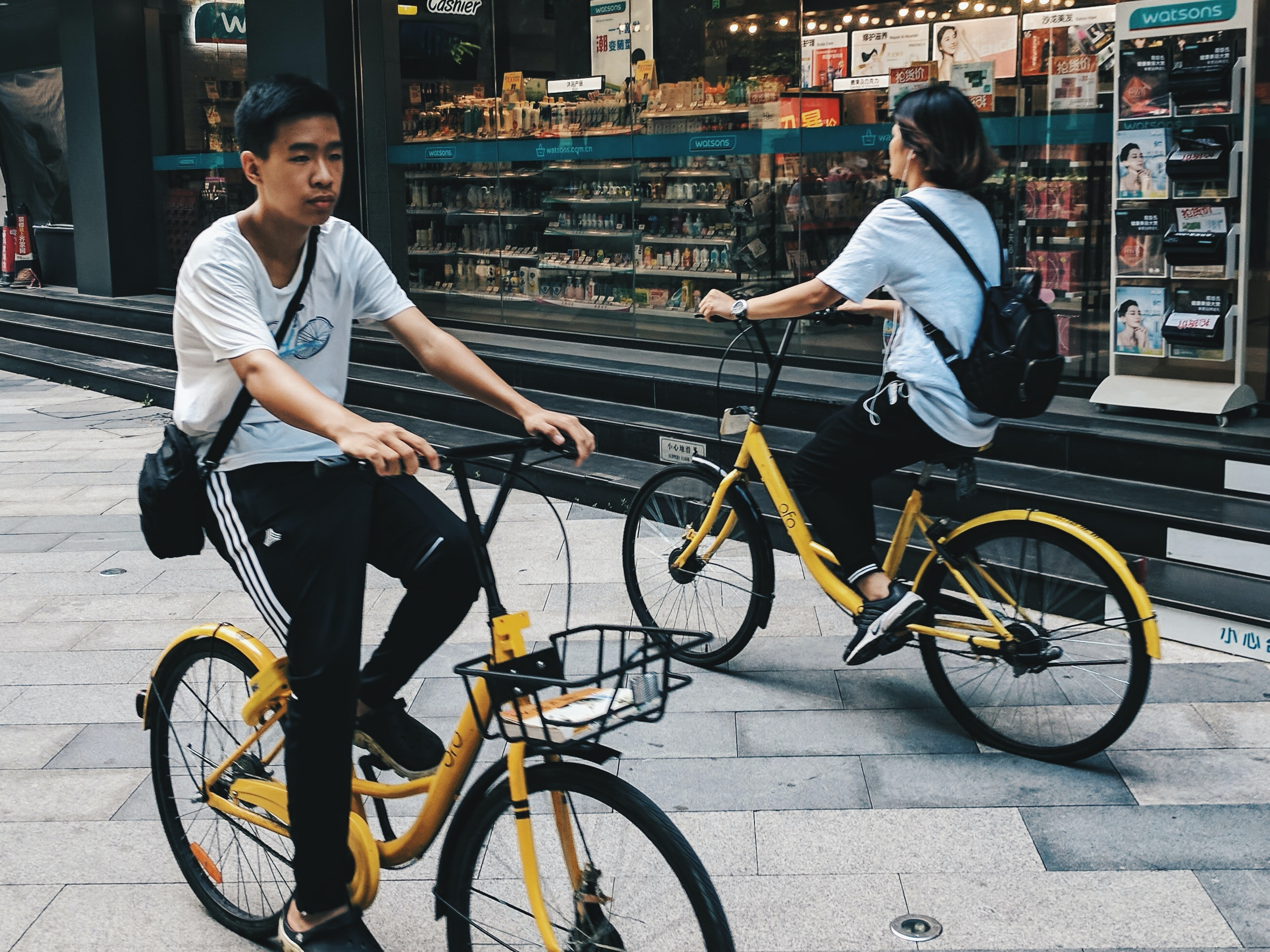 girl and boy riding yellow cruiser bikes beside store during daytime