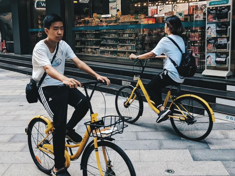 girl and boy riding yellow cruiser bikes beside store during daytime