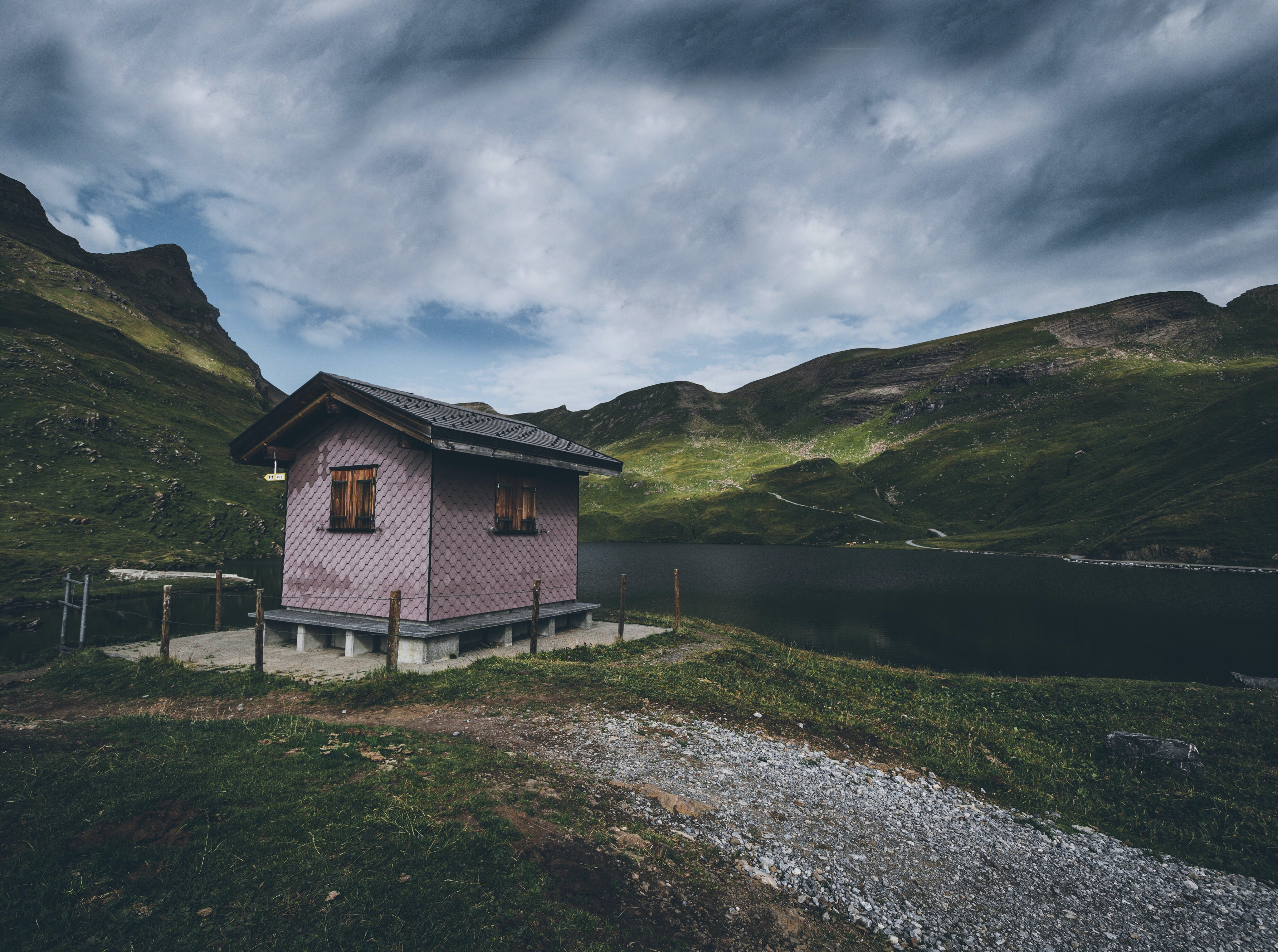 red and gray wooden house near lake surrounded by mountains