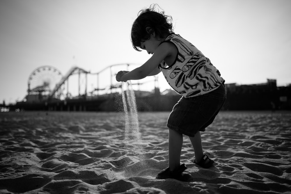 toddler playing beach sand