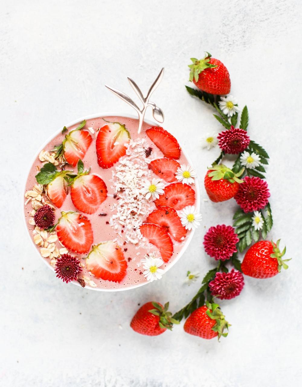 slice strawberry fruit on fruit shake with petaled flowers