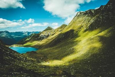 green mountain near lake at daytime