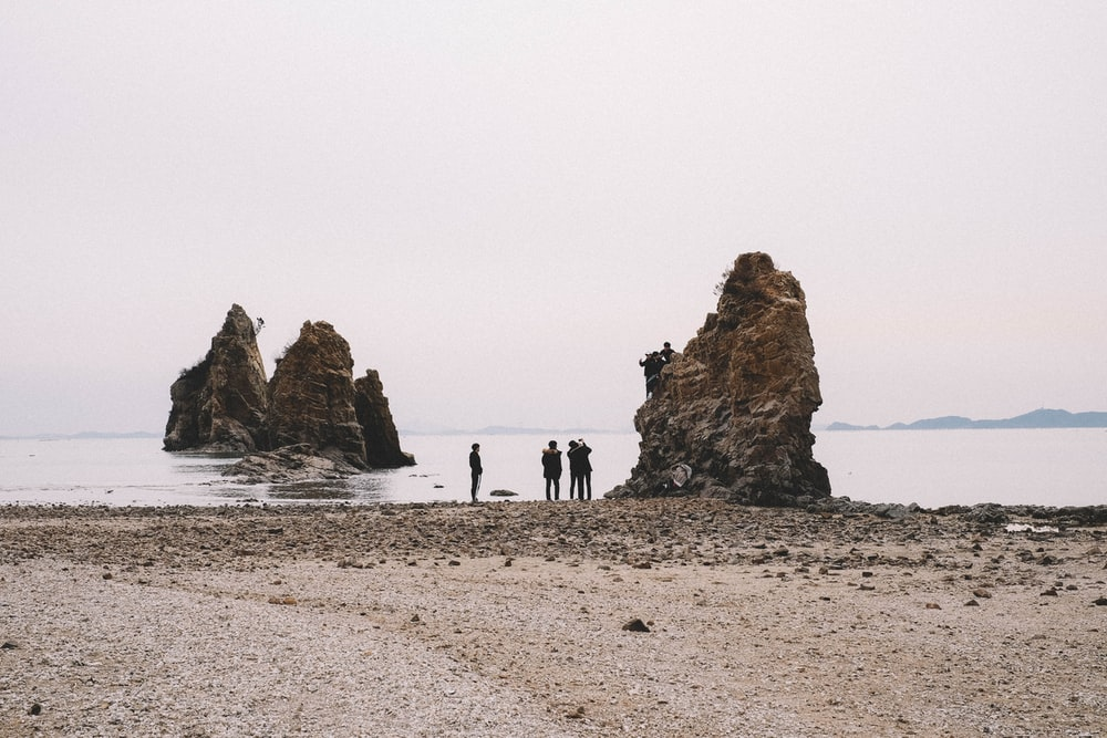 three people standing near brown rock formation