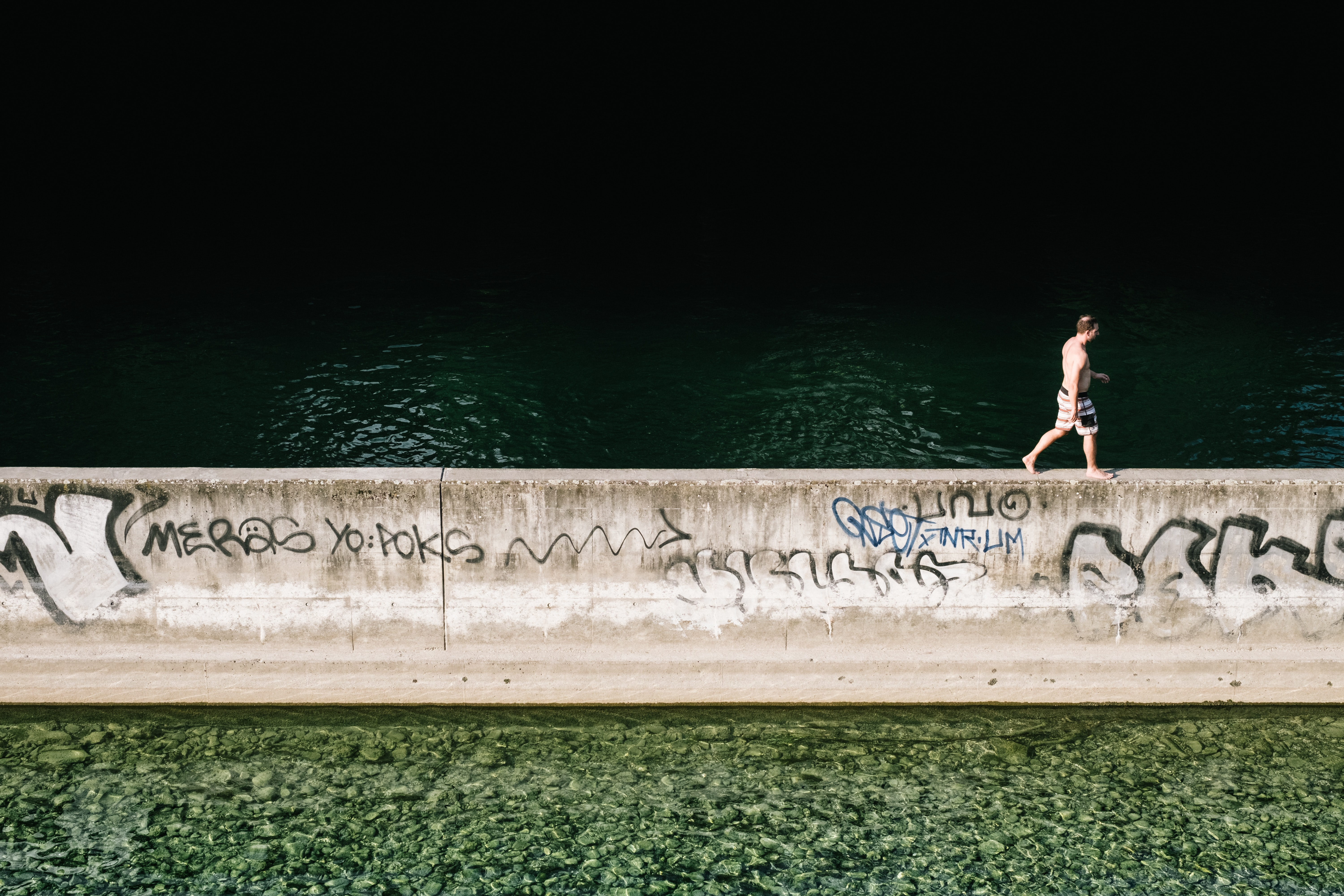 man walking on concrete wall beside lake