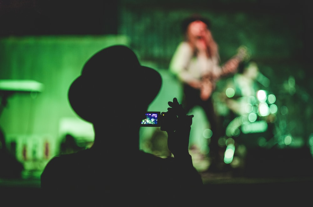 silhouette of man holding camcorder near woman singing on stage