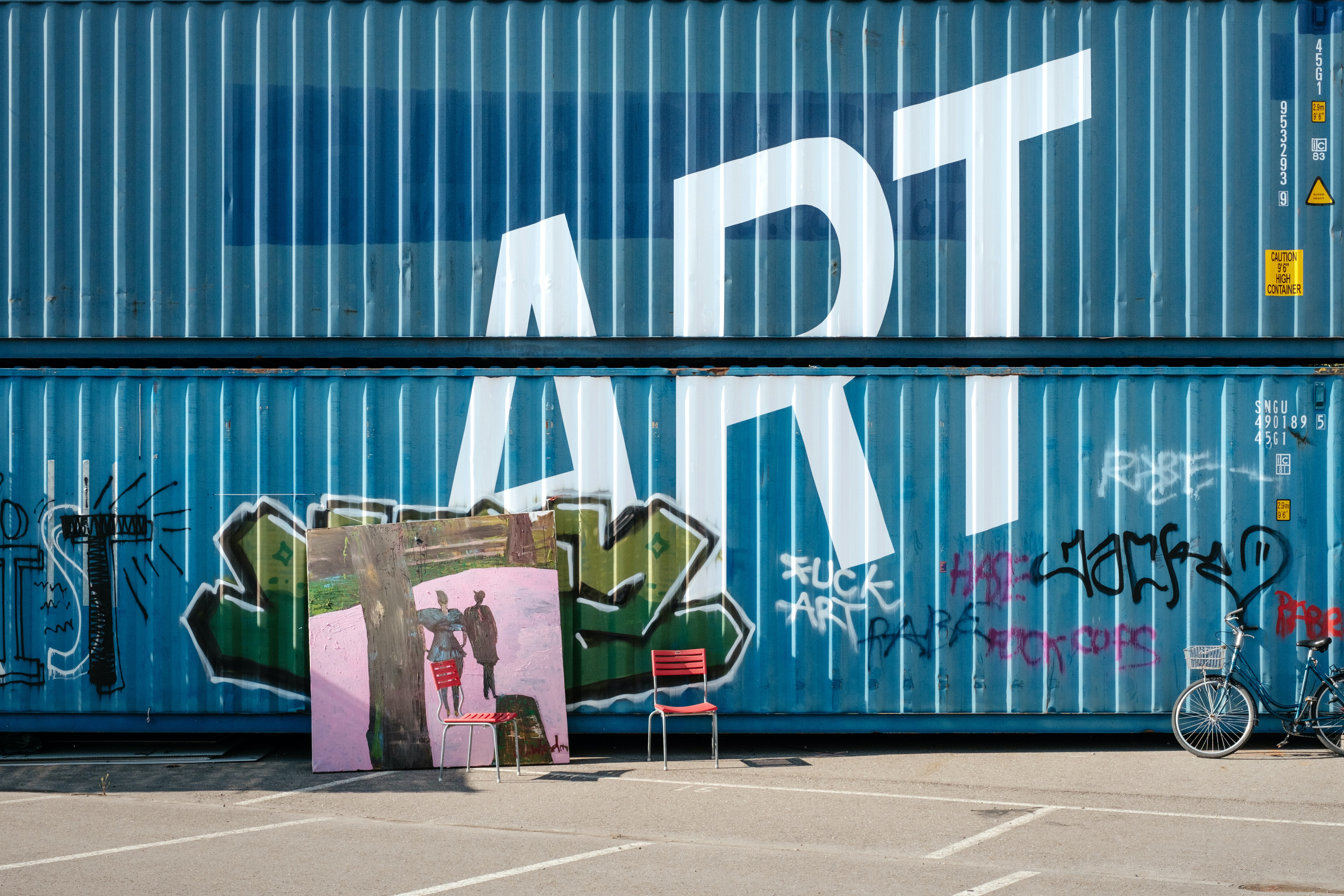 assorted-color graffiti on blue metal containers during daytime