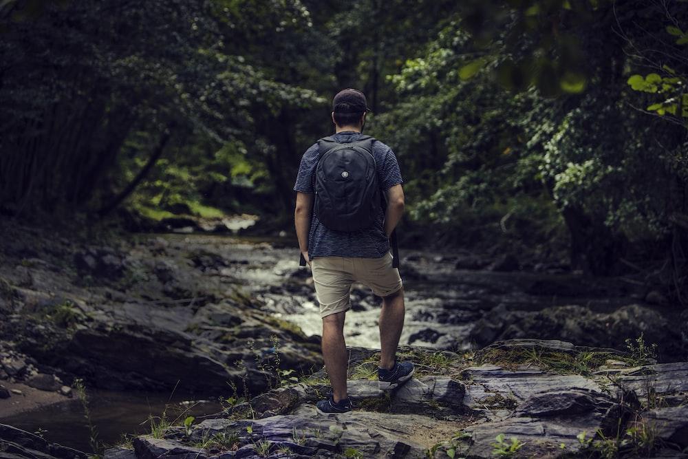 man standing on rock near body of water