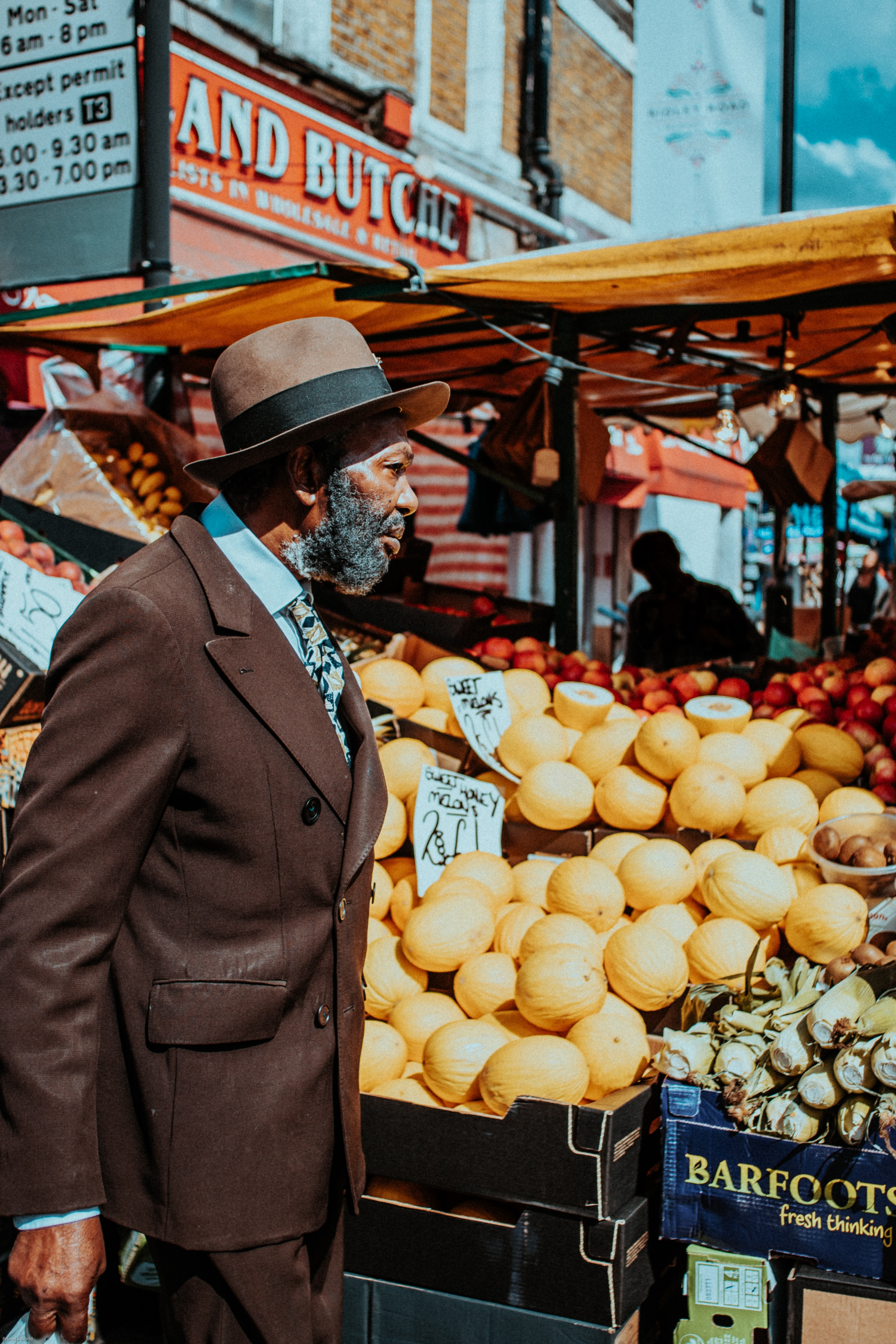 man in brown blazer standing on front of fruit displays near building
