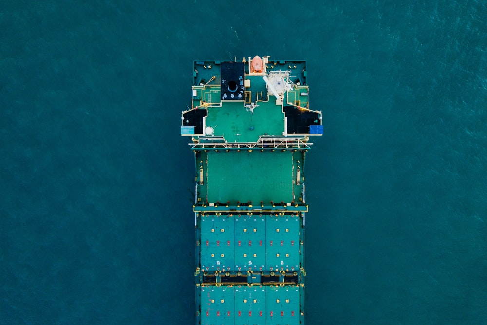 green cargo ship on body of water