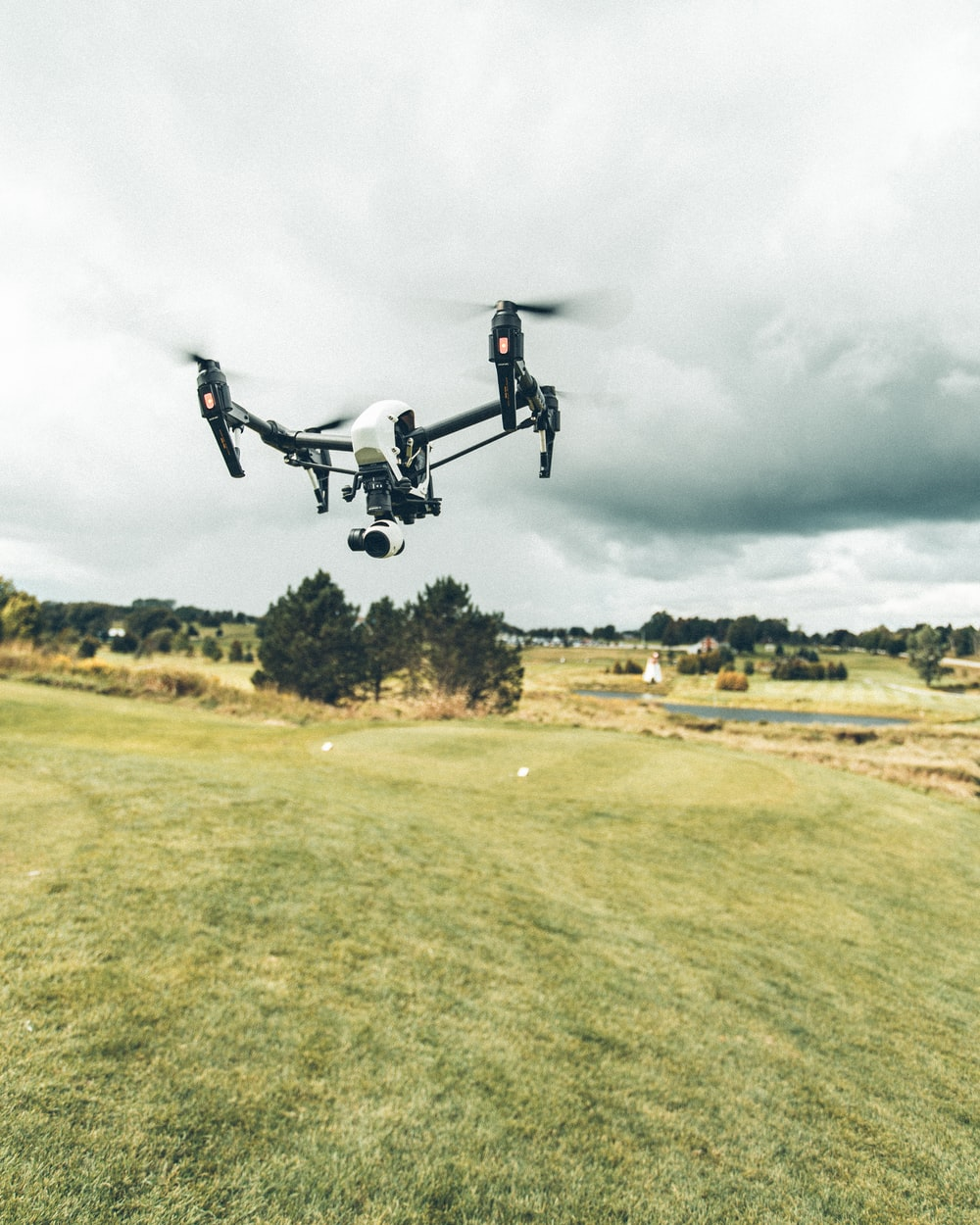 turned on white and black quadcopter drone