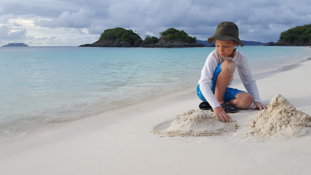 boy playing on sand under cloudy sky