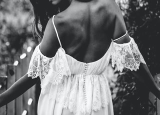 grayscale photo of woman wearing cold-shoulder backless dress
