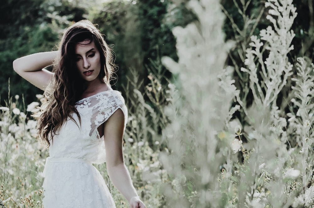 selective-focus photography of woman standing in a white flower field during daytime