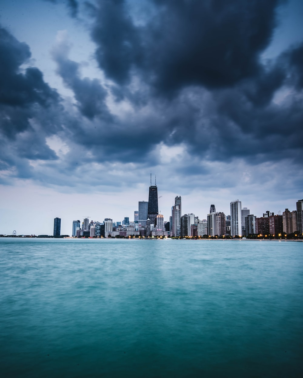 gray and black high-rise buildings beside body of water under gray and white sky at daytime