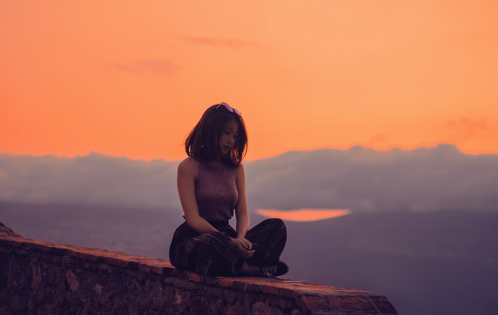 woman sitting on a cliff