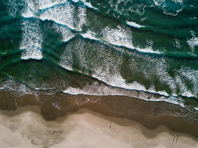 aerial photography of seawaves near seashore at daytime