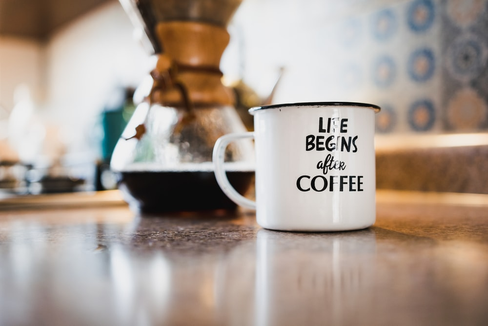 white and black life begins after coffee printed enamel cup beside 1/4 black liquid-filled glass flask on brown wooden panel