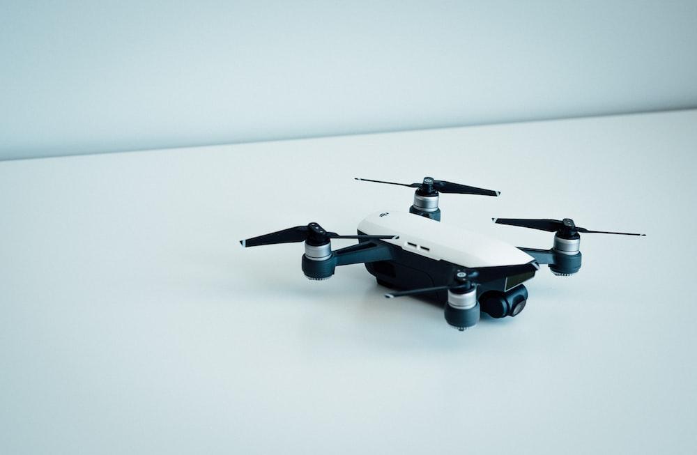 white and black quad copter drone